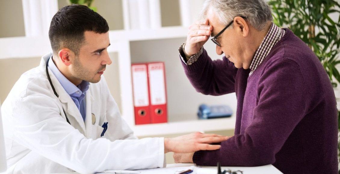 doctor listens to patient explaining headache
