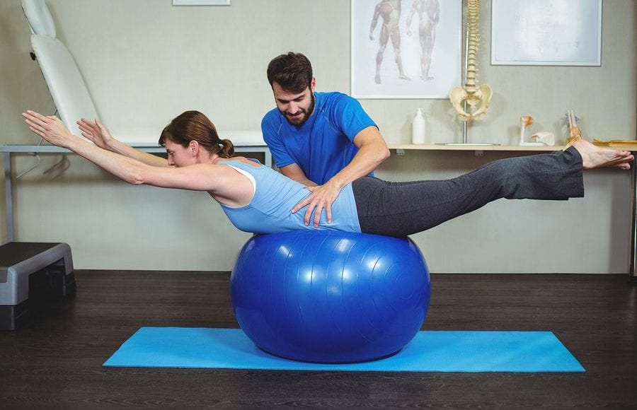 blog picture of Physiotherapist assisting woman on exercise ball in the clinic